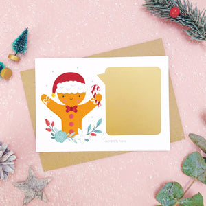 A personalised gingerbread man scratch card after the gold panel has been attached.Shot on a pink background with grey and green festive props.