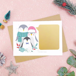 A personalised penguin family scratch card after the gold panel has been attached.Shot on a pink background with grey and green festive props.