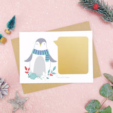 Load image into Gallery viewer, Penguin scratch card showing the gold panel after it has been stuck down. Shot on a pink background, surrounded with festive christmas props in tones of green and grey.
