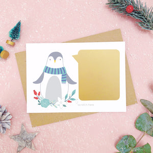 Penguin scratch card showing the gold panel after it has been stuck down. Shot on a pink background, surrounded with festive christmas props in tones of green and grey.