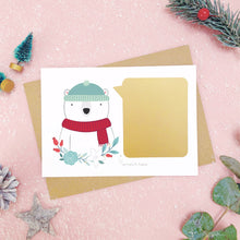 Load image into Gallery viewer, A personalised polar bear scratch card shot on a pink background with festive props in grey and green. Here the gold panel has been fixed and is ready to be scratched.