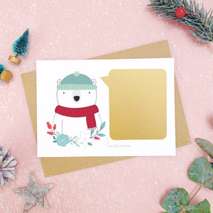 A personalised polar bear scratch card shot on a pink background with festive props in grey and green. Here the gold panel has been fixed and is ready to be scratched.