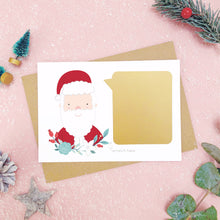 Load image into Gallery viewer, A santa scratch card with the gold panel attached to the front before it is scratched off. Shot on a pink background with green and grey festive props.
