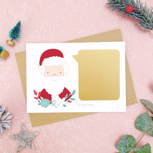 A santa scratch card with the gold panel attached to the front before it is scratched off. Shot on a pink background with green and grey festive props.