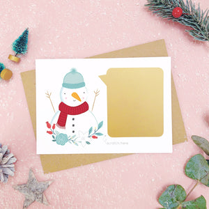 A personalised snowman scratch card after the gold panel has been attached.Shot on a pink background with grey and green festive props.