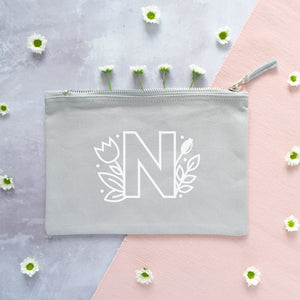 A grey cotton zipped pouch with a floral initial N printed in white.
