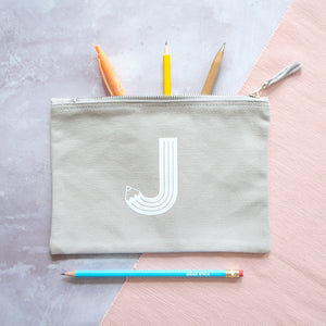 A grey cotton zipped pouch with a pencil initial J printed in white.