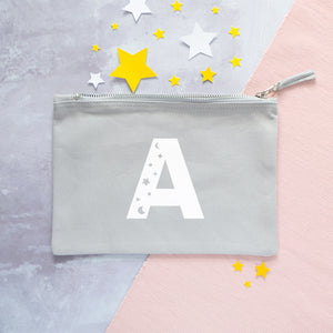 A grey cotton zipped pouch with a cosmic initial A printed in white.
