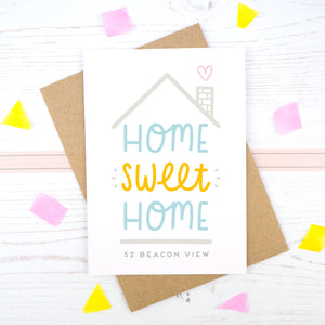 Home Sweet Home is a personalised card featuring the property number and road name. This version has a grey roof, a heart coming from the chimney and has 'home sweet home' in blue and orange.