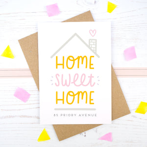 Home Sweet Home is a personalised card featuring the property number and road name. This version has a grey roof, a heart coming from the chimney and has 'home sweet home' in pink and orange.