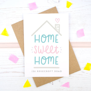 Home Sweet Home is a personalised card featuring the property number and road name. This version has a grey roof, a heart coming from the chimney and has 'home sweet home' in teal and pink.