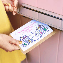 Load image into Gallery viewer, Joanne is pushing the Christmas wishes card featuring houses, snow and a snowman through the letter box of a pink door and wearing a yellow skirt.
