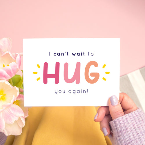 The non personalised, 'I can't wait to hug you again' card in pink. It has been shot on a pink background and has tulips to the left of the photo and is being held in the right.