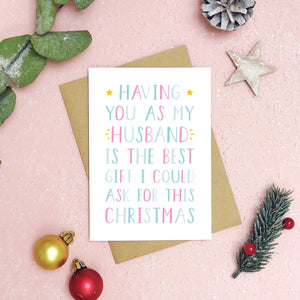 A 'best gift' husband Christmas card is on a pink background with foliage, baubles and Christmas props. The writing on the card is blue and pink.