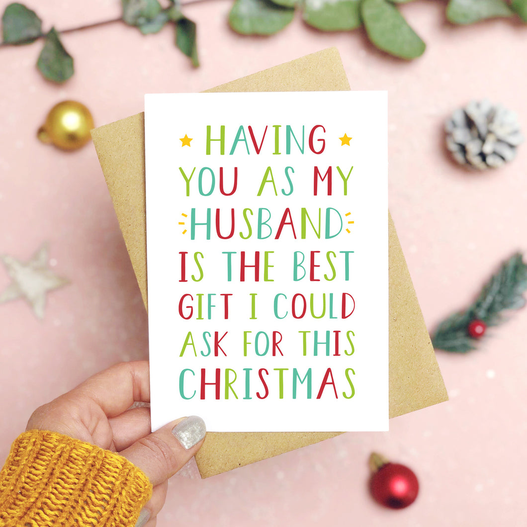 A 'best gift' husband Christmas card held over a pink background by a hand in a mustard knit jumper with foliage and baubles in the background. The writing on the card is red and green.