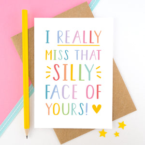 I really miss that silly face of yours card in rainbow, shot on a pink background with a yellow pencil.