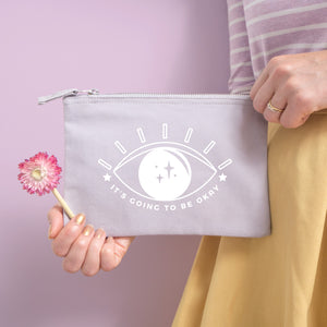 It's going to be okay cotton pouch in grey with white text and all seeing eye. Photographed on a pink background with a model holding the pouch with dried flowers, a stripy top and yellow skirt.