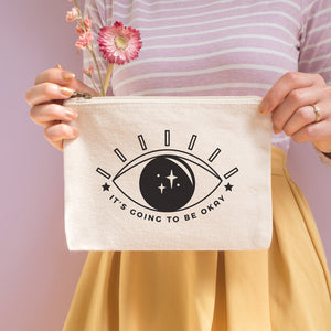 It's going to be okay cotton pouch in natural with black text and all seeing eye. Photographed on a pink background with a model holding the pouch with dried flowers, a stripy top and yellow skirt.