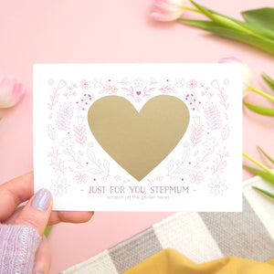 A personalised just for you stepmum scratch card showing how the card looks before the golden heart is scratched off to reveal the message. Shot on a pink background with tulips.