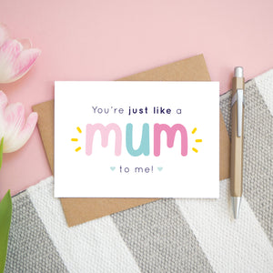 A flatlay set up of the pink and blue version of the 'you're just like a mum to me' card. It is landscape in orientation and is photographed next to a pen and pink tulips for scale.