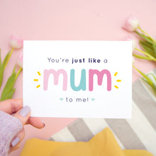 Load image into Gallery viewer, You're just like a mum to be me card in pink and blue being held in the left hand over a pink, white and grey background with tulips.
