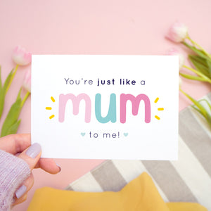 You're just like a mum to be me card in pink and blue being held in the left hand over a pink, white and grey background with tulips.