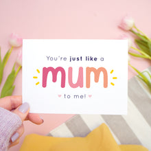 Load image into Gallery viewer, You're just like a mum to be me card in pink and peach being held in the left hand over a pink, white and grey background with tulips.