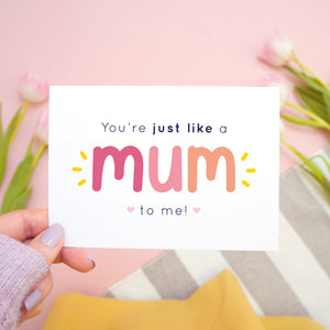 You're just like a mum to be me card in pink and peach being held in the left hand over a pink, white and grey background with tulips.