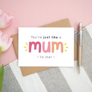 A flatlay set up of the pink and peach version of the 'you're just like a mum to me' card. It is landscape in orientation and is photographed next to a pen and pink tulips for scale.