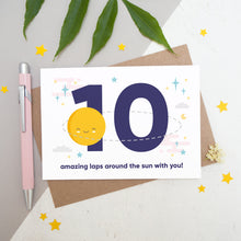 Load image into Gallery viewer, Laps around the sun anniversary card featuring a sun orbiting the number 10 surrounded by stars. Flat lay image shot on a white and grey background with some foliage, yellow stars and a pink pen.