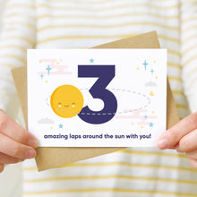 Load image into Gallery viewer, Laps around the sun anniversary card featuring a sun orbiting the number 3 surrounded by stars. Shot as a lifestyle image with someone in a white and yellow striped jumper holding the card.