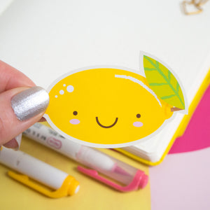A lemon sticker held over a blank bullet journal page and with pens blurred out in the background.