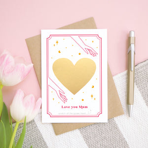 A personalised 'love you...' card before the gold heart has been scratched off. It has been shot on a pink background, with tulips and a pen for scale.