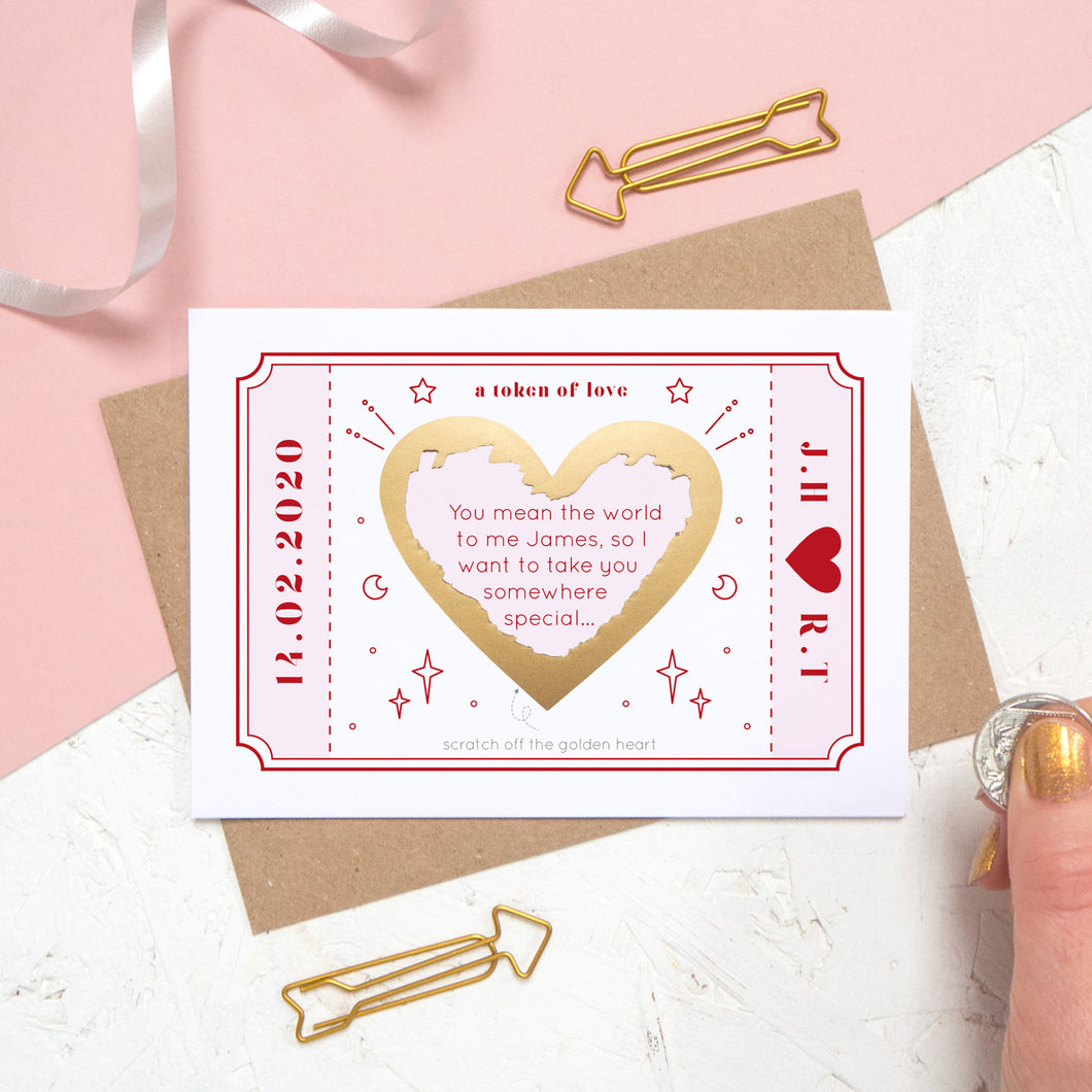 The personalised Love Token Scratch card with the printed message scratched off. Shot on a pink and white background with a hand in the corner.