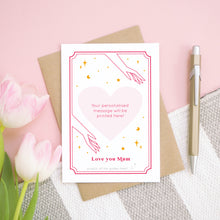 Load image into Gallery viewer, A personalised 'love you...' scratch card showing what the card will look like if all of the heart is scratched off. It has been shot on a pink background, with tulips and a pen for scale.
