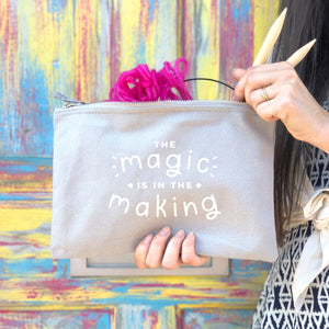 The magic is in the making large project pouch in grey with a white print and a knitting project.