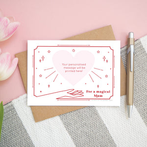 A personalised 'magical mum' scratch card showing how the card will look once all of the gold heart has been removed. The card is shot from above on a pink, white and grey background with a pen for scale.