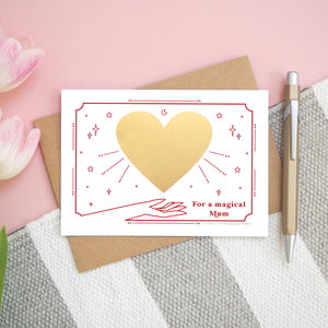 A personalised 'magical mum' scratch card before the gold heart is scratch off. Card is photographed from above on a pink, white and grey background with a pen for scale.