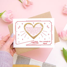 Load image into Gallery viewer, A personalised 'magical mum' scratch card showing how your personalised message could look with the gold heart scratched off. The card is being held over a pink background with pink tulips.