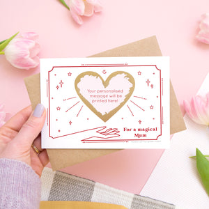 A personalised 'magical mum' scratch card showing where your personalised message is printed with the gold heart scratched off. The card is being held over a pink background with pink tulips.