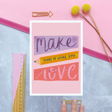 Load image into Gallery viewer, Make more of what you love print with a pink background and purple, yellow and dark pink shapes filled with lettering. Photographed on a marble and pink background