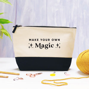 A make your own magic cotton storage bag, natural in colour with a black box bottom base photographed on a purple background with leaves, a ball of yarn and crochet tools.