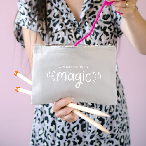 Maker of magic cotton project pouch, in size large and colour grey being held by Joanne Hawker in a leopard print jumpsuit with bright pink yarn and knitting needles.