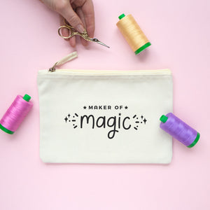 Magic of magic, medium cotton project pouch in colour natural surrounded by reels of cotton and sewing scissors.