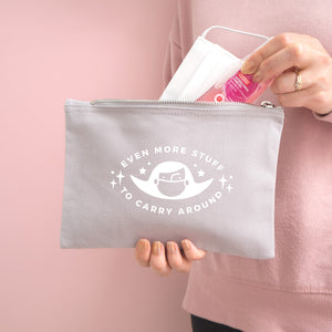 Even more stuff to carry around zipped cotton pouch in grey with white text. Photographed on a pink background. Model is holding the pouch with a face mask and hand sanitiser.