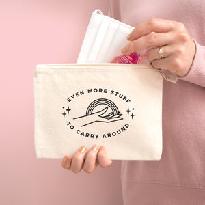Even more stuff to carry around zipped cotton pouch in natural with black text. Photographed on a pink background. Model is holding the pouch with a face mask and hand sanitiser.