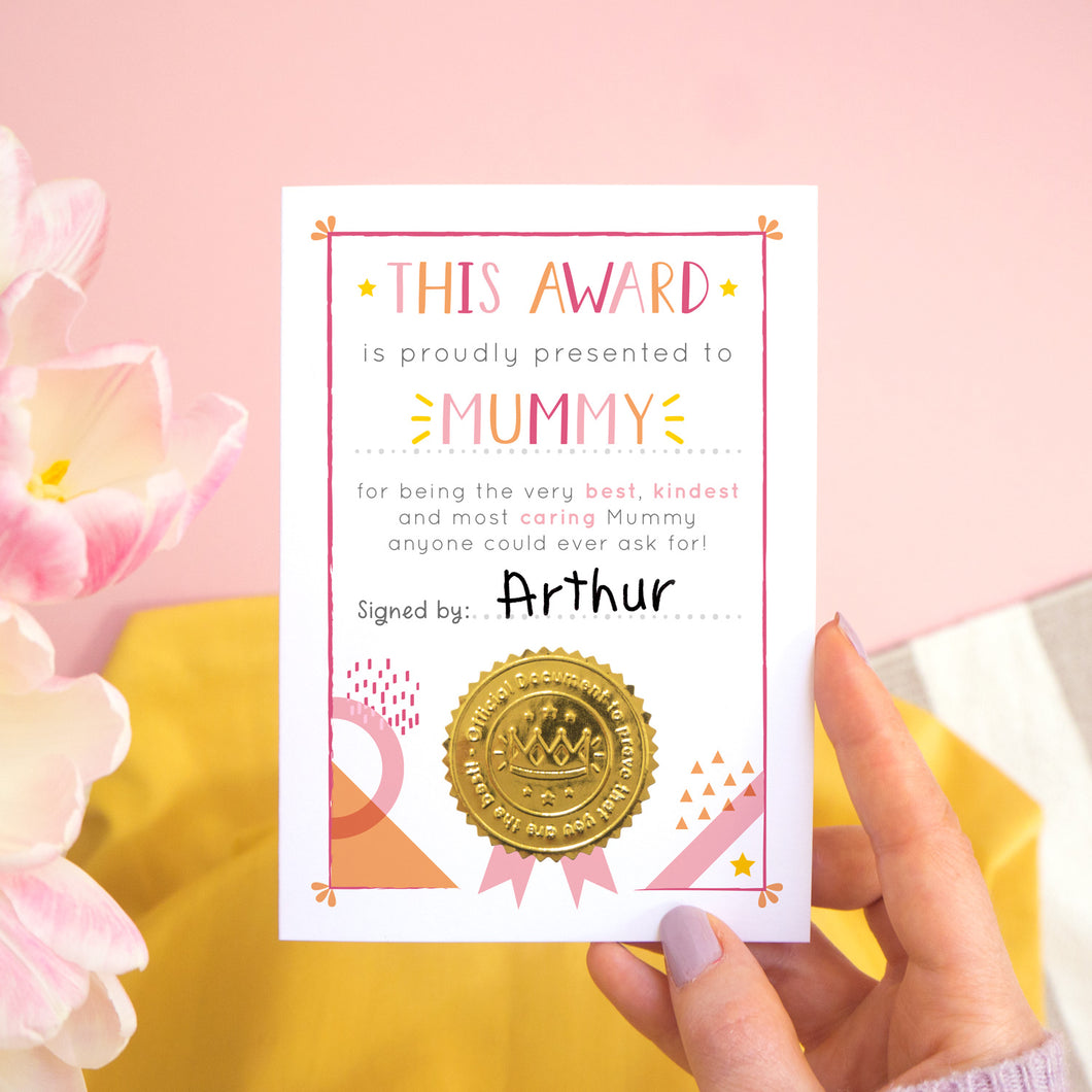 A Mummy certificate card for mother's day featuring a shiny gold seal. This card is pink and peach in colour with a small pop of yellow and has been shot over a pink and yellow background with tulips to the side.