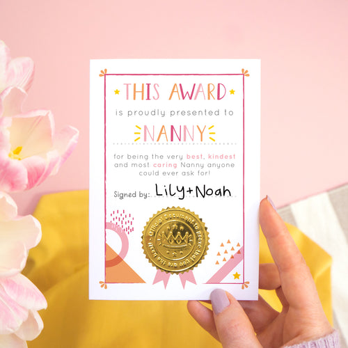 A Nanny certificate card for mother's day featuring a shiny gold seal. This card is pink and peach in colour with a small pop of yellow and has been shot over a pink and yellow background with tulips to the side.