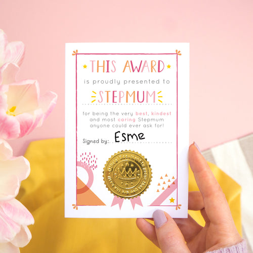 A stepmum certificate card for mother's day featuring a shiny gold seal. This card is pink and peach in colour with a small pop of yellow and has been shot over a pink and yellow background with tulips to the side.