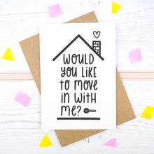 Load image into Gallery viewer, Would you like to move in with me card in black & white, under a roof with a chimney and heart.